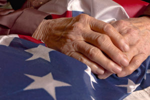 elderly hands of a veteran resting on the american flag